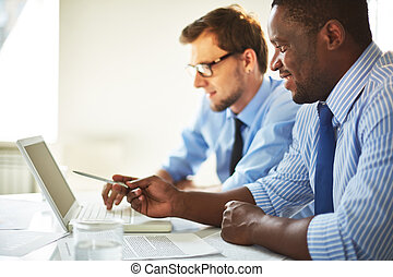 Presentation - Image of two young businessmen using laptop...
