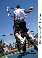Men Playing Basketball - A young basketball player driving...