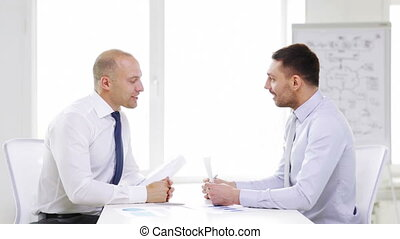 two smiling businessmen with charts in office - business,...