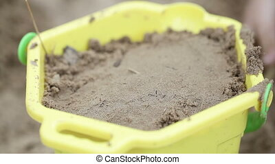 Pail with sand - Child plays with a bucket and sand