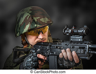sniper aiming a machine gun - Young handsome soldier...
