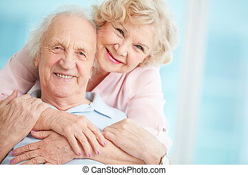 Embrace - Happy and affectionate elderly couple posing for...