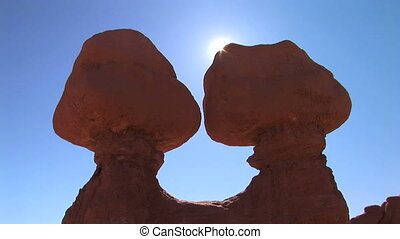 Sun peeks behind rock formations, time lapse - Sun traveling...