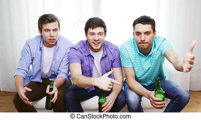 upset male friends with beer watching tv at home