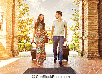 Young couple standing at hotel corridor upon arrival,...