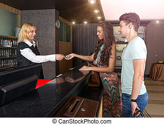 Receptionist - the hotel - give the young couple a room key