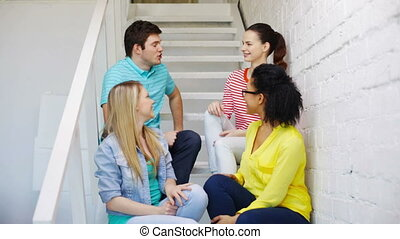 smiling students sitting on stairs and talking - education,...