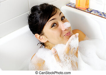 Happy gorgeous young woman having fun with foam in bath tub...