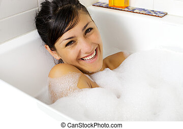 Smiling beautiful young woman in bathtub full of foam -...