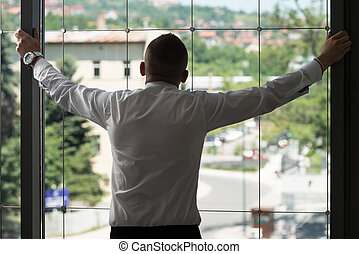Businessman Looking Through Office Window