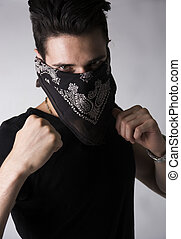 Man in a bandanna balling his fists aggressively - Man with...