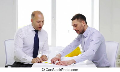 two smiling businessmen or architects in office - business,...