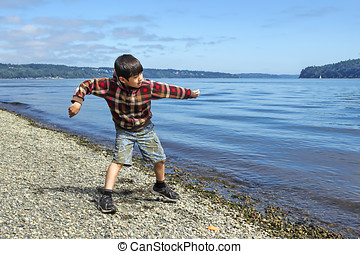 Boy skips a rock in the water - A young boy skips a rock on...