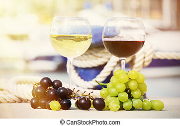 Pair of wineglasses and grapes against yachts in La Spezia,...
