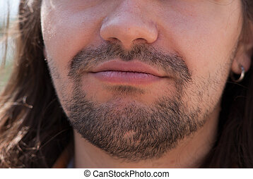 Part of face young European man with beard. Smiles.