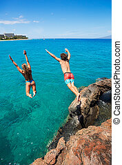 Friends cliff jumping into the ocean