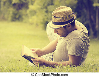 Man reading a book on the grass