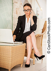 Busy working. Confident young woman in formalwear working on...