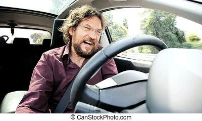Man laughing while driving car