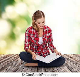 smiling young woman sitting on floor with book