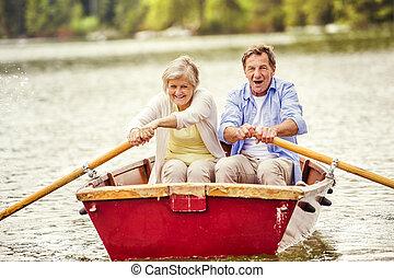 Senior couple on boat - Senior couple paddling on boat on...