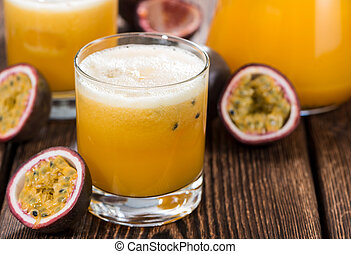 Glass with Maracuja Juice and fresh fruits on wooden...