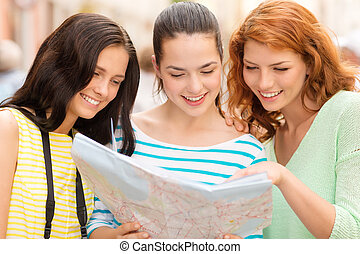 smiling teenage girls with map and camera - tourism, travel,...