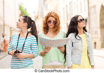 teenage girls with map and camera - tourism, travel,...
