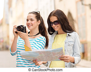 smiling teenage girls with map - tourism, travel, leisure,...
