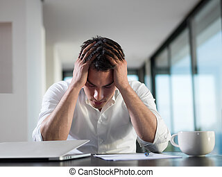 frustrated young business man working on laptop computer at...