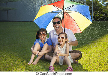 Father and two daughters sitting on a meadow with colorful umbre