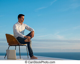 relaxed young man at home on balcony - handsome young man...
