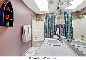 Simple bathroom intrerior in mauve color with skylight -...