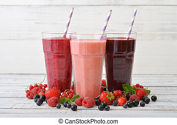 Smoothies with different berries - Three glasses of...