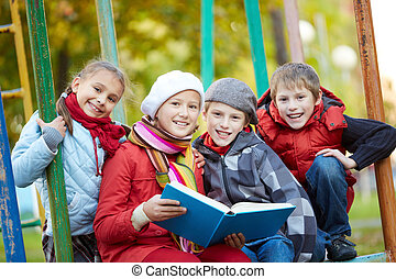 Reading book - Portrait of happy schoolkids reading book...