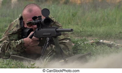 Sniper Shoots at a Target - Sniper in camouflage and...