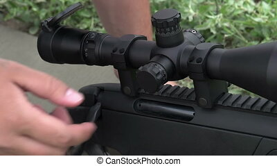 Configuring the Optical Sight - Closeup hand adjusts the...