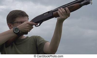 Recharging Shotgun - Hunter in camouflage jacket fires his...