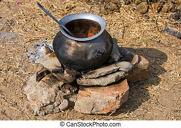 Metal pot with food on fire, India - Metal pot with food on...