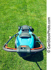 blue lawn mower on green grass