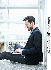 Young man browsing the internet on laptop