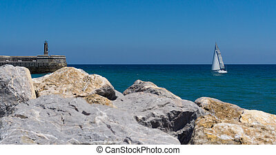 Stone Lighthouse and sailing boat - Old small stone...