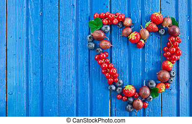 Background with fresh berries - Blue wooden background with...