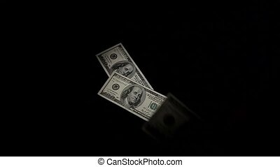 considers money isolated on black background. Slow Motion.