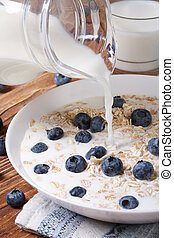 oatmeal with blueberries and milk is poured from a jug on...