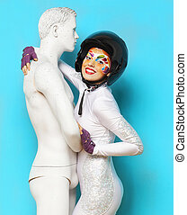 Model with bright creative make up with helmet and male...