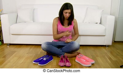 Happy girl deciding the shoe to put on