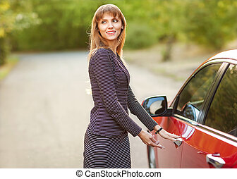girl want open door of red car outside