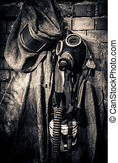 protective suit with gas mask - An einer Wand hängender...
