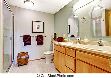 Bright bathroom interior with honey vanity cabinet - Light...